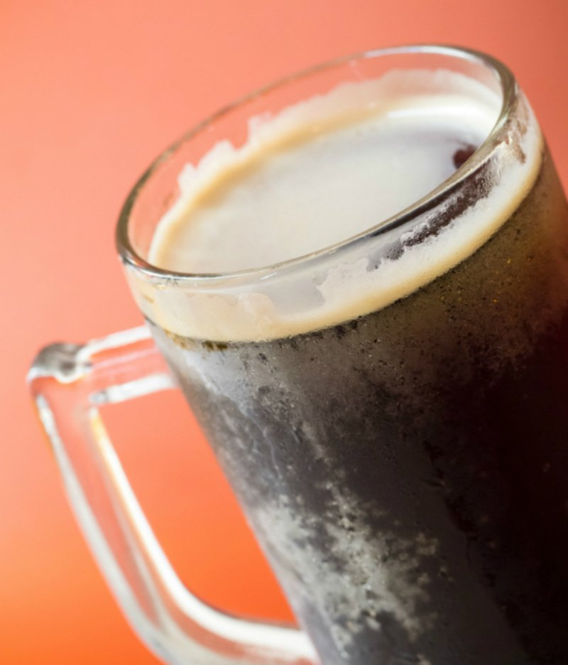 Closeup shot of root beer glass isolated on orange background